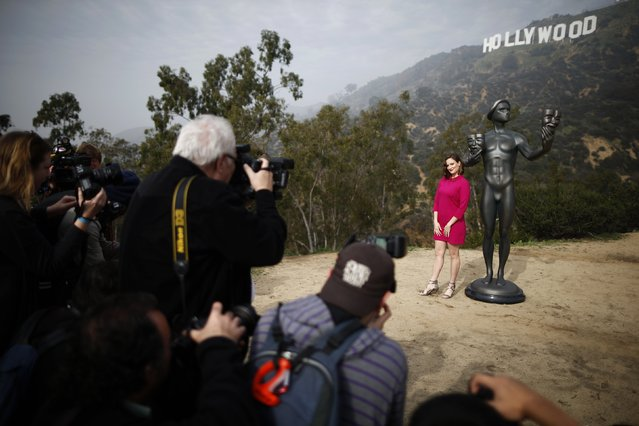 Media members photograph actress Julie Lake standing next to a Screen Actors Guild statue in front of the Hollywood sign in Los Angeles, California January 20, 2015. (Photo by Lucy Nicholson/Reuters)