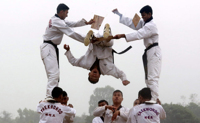 """Members of the Indian Army display aerobatic Taekwondo skills, during the 10th Reunion and 255th Anniversary of Army Service Crops in Bangalore, India, 09 December 2015. Korean Martial Art """"Taekwondo"""" is an art of kicking and punching that been introduced in the ASC in 1990 for self-defense. Indian Army Service Corps, established in 1760, is an arm of the Indian Army handling logistic support. (Photo by Jagadeesh N.V./EPA)"""