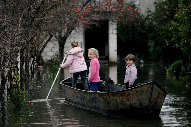 Children use a boat at a flooded area in Obot village, near Shkodra, Albania on January 12, 2021. (Photo by Florion Goga/Reuters)