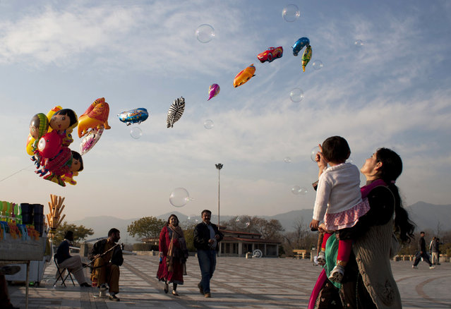 A Pakistani woman shows her daughter bubbles released by a vendor in Lake View park in Islamabad, Pakistan, Saturday, January 24, 2015. (Photo by Shakil Adil/AP Photo)