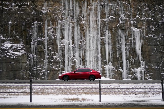 A motorist drives past a rock wall covered with ice on Interstate 71 as snow begins to fall in Louisville, Kentucky, U.S., February 15, 2021. (Photo by Bryan Woolston/Reuters)