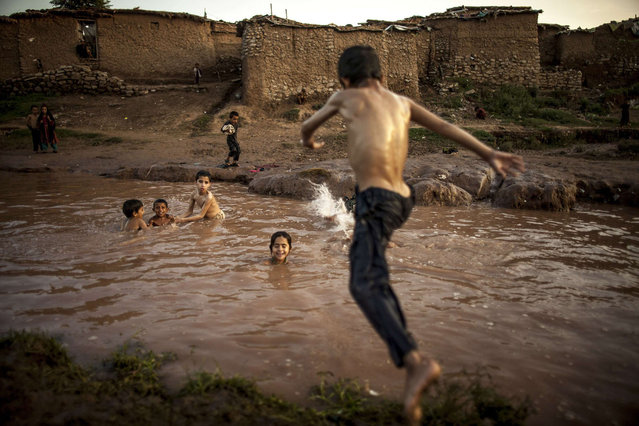 A boy, whose his family fled military operations in the western tribal area, jumps into a stream in a slum on the outskirts of Islamabad July 8, 2013. (Photo by Zohra Bensemra/Reuters)