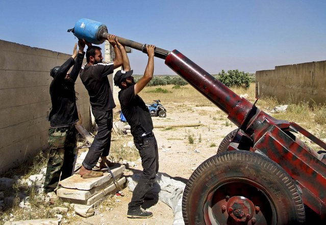Free Syrian Army fighters prepare to fire a mortar shell during what they say is an offensive against forces loyal to Syria's President Bashar al-Assad, in Idlib, on July 17, 2013. (Photo by Abdalghne Karoof/Reuters)