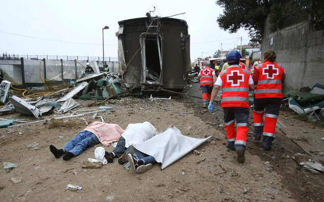 Emergency personnel respond to the scene of a train derailment in Santiago de Compostela, Spain, Wednesday, July 24, 2013. A train derailed in northwestern Spain on Wednesday night, toppling passenger cars on their sides and leaving at least one torn open as smoke rose into the air. Dozens were feared dead, with possibly even more injured. (Photo by Antonio Hernandez/AP Photo/El correo Gallego)