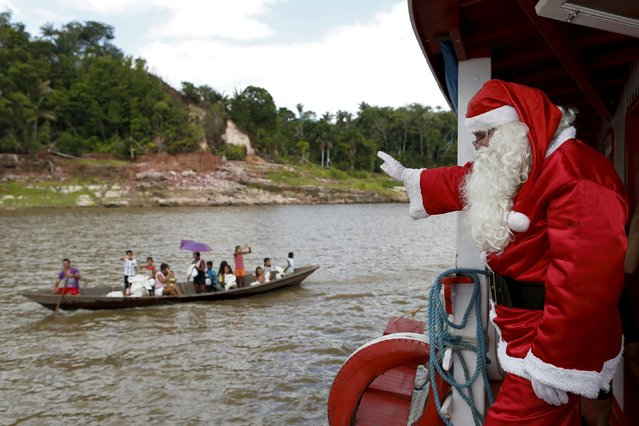 Claudionor Jose de Deus, wearing a Santa Claus costume, waves to people on a boat in the Amazon River, in rural Manaus, Brazil, December 19, 2015. Jose de Deus is part of a volunteer group that distributes toys to children from poor neighborhoods and riverside communities that are distant from the city. (Photo by Bruno Kelly/Reuters)
