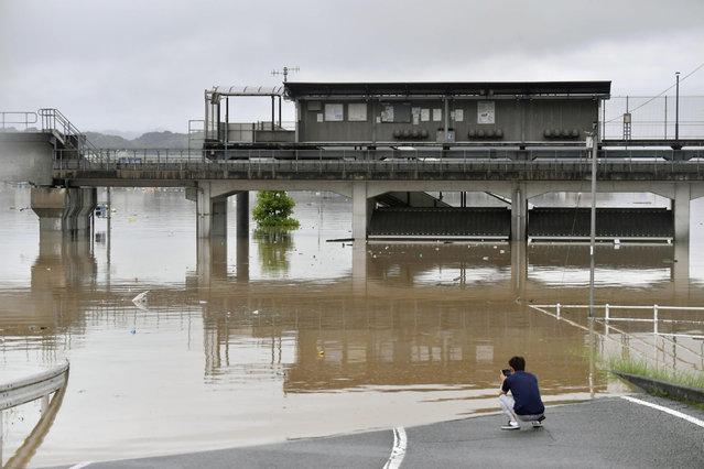 A man uses smartphone at a flooded area near Kawabejuku train station after heavy rains in Kurashiki, Okayama prefecture, southwestern Japan, Saturday, July 7, 2018. Torrents of rainfall and flooding continued to batter southwestern Japan. (Photo by Koki Sengoku/Kyodo News via AP Photo)