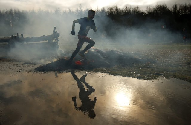 A competitors run through smoke and flames during the Tough Guy event in Perton, central England, February 1, 2015. (Photo by Phil Noble/Reuters)