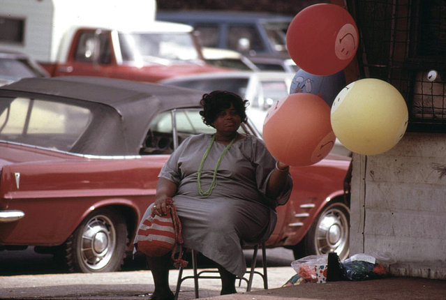 """Woman selling """"Have A Nice Day"""" balloons on a Chicago South Side street corner at Sox Park Baseball Field, June 1973. (Photo by John H. White/NARA via The Atlantic)"""