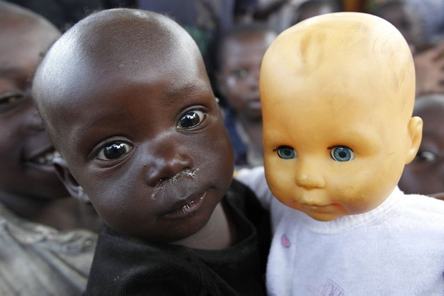 A Congolese girl holds a doll at the child friendly space within Mugunga III camp for the internally displaced people near Goma, eastern Democratic Republic of Congo, on August 8, 2013. (Photo by Thomas Mukoya/Reuters)