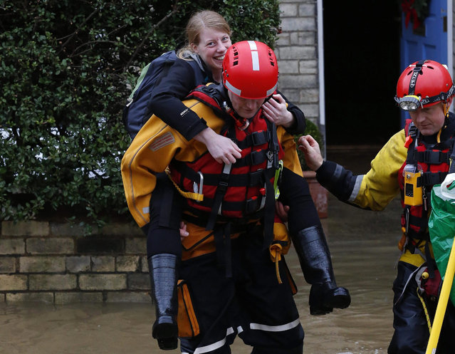 Rescue service workers evacuate residents from their flooded homes in York city centre, North Yorkshire, Britain, 28 December 2015. The nearby river Ouse burst its banks after heavy rainfall over Christmas and Boxing Day, causing widespread flooding across the north of Britain with many residents being evacuated by rescue services. (Photo by Lindsey Parnaby/EPA)