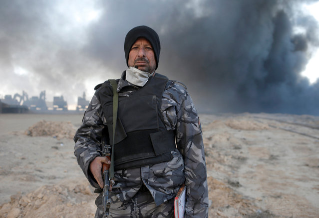 A policeman stands in front of oilfields burned by Islamic State fighters in Qayyara, south of Mosul, Iraq November 23, 2016. (Photo by Goran Tomasevic/Reuters)