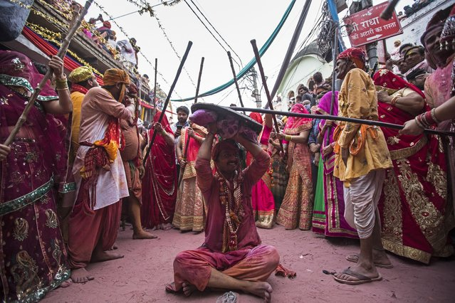 Hindu women beat a man with sticks as they traditionally celebrate the Lathmar Holi, the spring festival of colours near a temple in Barsana village of India's Uttar Pradesh state on March 23, 2021. (Photo by Xavier Galiana/AFP Photo)