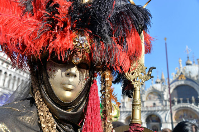 A dressed-up carnival reveller poses on the dock at San Marco Square during the second day of Carnival in San Marco Square, in Venice, Italy, February 8, 2015. (Photo by Andrea Merola/EPA)