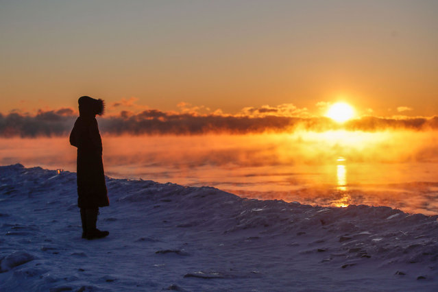A man walks along Lake Michigan as the sun rises in Chicago, Illinois, on February 7, 2021. According to the National Weather Service, dangerous wind chills can bring temperatures to up to 25 degrees Fahrenheit below zero in the Chicago area on Sunday. (Photo by Kamil Krzaczynski/AFP Photo)