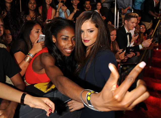 Selena Gomez poses with a fan at the MTV Video Music Awards on Sunday, August 25, 2013, at the Barclays Center in the Brooklyn borough of New York. (Photo by Scott Gries/AP Photo/Invision)