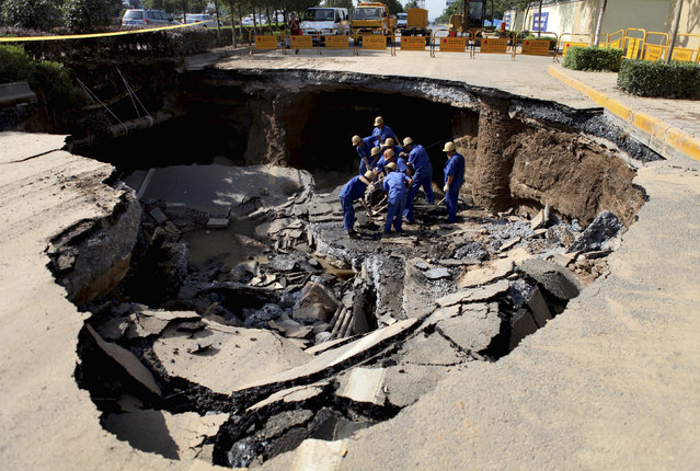 Workers repair a cave-in area on a road in Xi'an, Shaanxi province May 27, 2012. The cause of the cave-in, measuring about 6 meters (20 ft.) in depth, 15 meters (49 ft.) in length and 10 meters (33 ft.) in width, is still under investigation. No casualty has been reported, according to local media. (Photo by Reuters/China Daily)