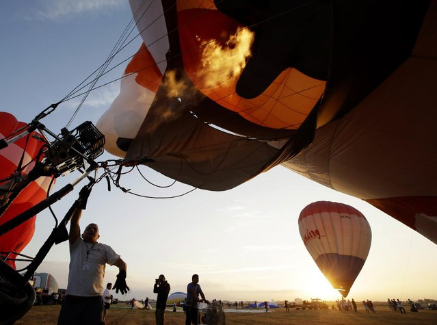 Hot air balloons are inflated as they take part in the 19th Philippine Hot Air Balloon festival Thursday, February 12, 2015 at Clark Economic Zone, Pampanga province north of Manila, Philippines. (Photo by Bullit Marquez/AP Photo)