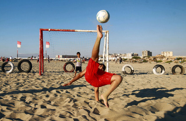 A boy kicks a ball while shooting at a football net along a beach in Libya's eastern coastal city of Benghazi on August 22, 2020. (Photo by Abdullah Doma/AFP Photo)
