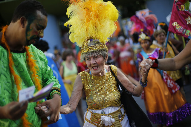"An elderly patient from the Nise de Silveira mental health institute dances in costume during the institute's carnival parade, coined in Portuguese: ""Loucura Suburbana"", or Suburban Madness, at the center in Rio de Janeiro, Brazil, Thursday, February 12, 2015. (Photo by Silvia Izquierdo/AP Photo)"