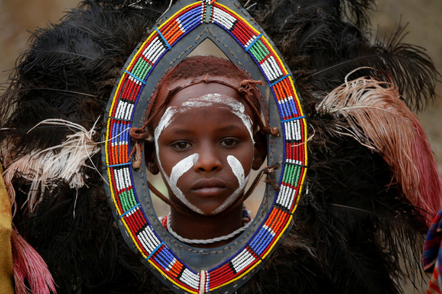 A Maasai boy wears a traditional costume during an initiation into an age group ceremony near the town of Bisil, Kajiado county, Kenya, August 23, 2018. (Photo by Baz Ratner/Reuters)