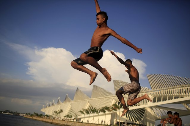 "Boys dive into the Guanabara Bay in front of the ""Museu do Amanha"" (Museum of Tomorrow), in the port of Rio de Janeiro, Brazil, January 8, 2016. (Photo by Pilar Olivares/Reuters)"