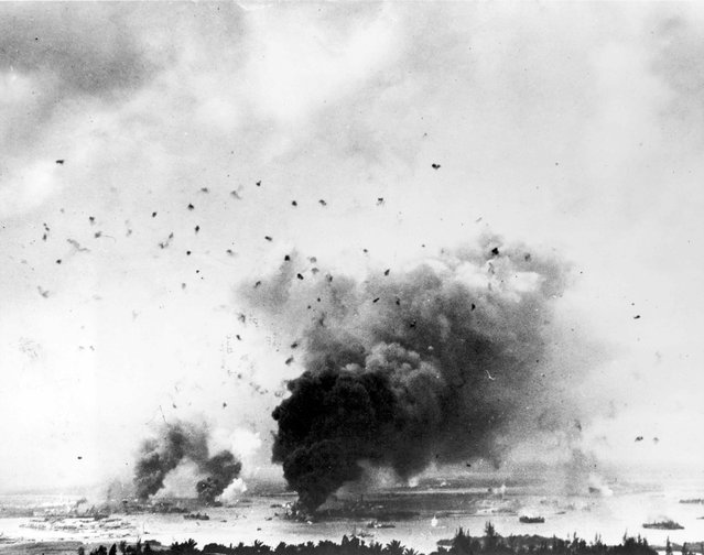 Flak bursts of anti-aircraft shells pepper the skyline above rising smoke from the battleship USS Arizona during the Japanese raid on Pearl Harbor, Hawaii, U.S. December 7, 1941. (Photo by Reuters/U.S. Navy/National Archives)