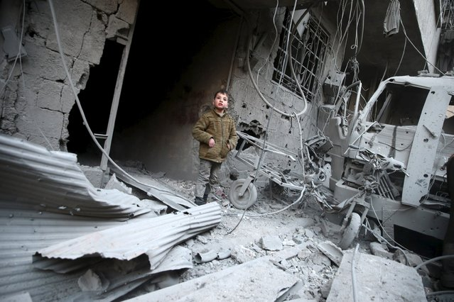 A boy inspects damage in a site hit by what activists said were airstrikes carried out by the Russian air force in the town of Douma, eastern Ghouta in Damascus, Syria January 10, 2016. (Photo by Bassam Khabieh/Reuters)