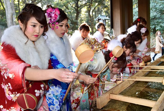 Twenty-year-old female tour guides dressed in traditional kimonos wash their mouths and hands at Tokyo's Meiji shrine before attending a purification ceremony with a Shinto priest to celebrate Japan's Coming-of-Age Day on January 8, 2016. Since tour guides will be busy working on Japan's national holiday Coming-of-Age Day on January 11, the company held a ceremony. Young people turning 20 are officially recognised as adults in Japan. (Photo by Yoshikazu Tsuno/AFP Photo)