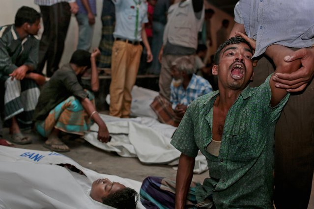 Bangladeshi relatives wail near bodies of victims after a river ferry carrying about 100 passengers capsized Sunday after being hit by a cargo vessel,in Manikganj district, about 40 kilometers (25 miles) northwest of Dhaka, Bangladesh, Sunday, February 22, 2015. (Photo by A. M. Ahad/AP Photo)
