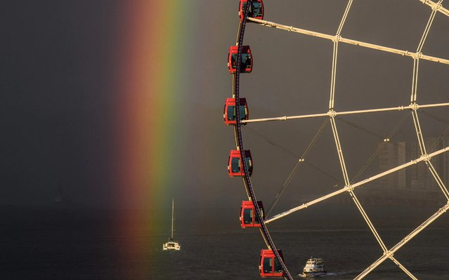 Passengers (top C) sit in a ferris wheel as a rainbow appears during sunset after a rain shower in Hong Kong on June 16, 2020. (Photo by Anthony Wallace/AFP Photo)