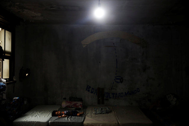 A child, relative of a member of the roofless movement who lives together with members of lesbian, gay, bisexual and transgender (LGBT) community, that have been invited to live in a building that the movement has occupied, sleeps, in downtown Sao Paulo, Brazil, November 28, 2016. (Photo by Nacho Doce/Reuters)