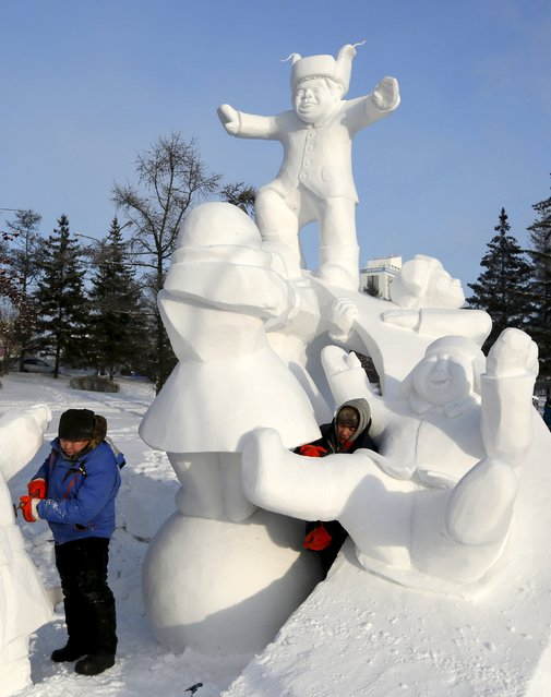 """Participants from the Yakutia region work on a snow sculpture called """"Happiness"""", on the last day of the annual international festival of snow and ice sculptures """"The Magical Ice of Siberia"""", in Krasnoyarsk, Russia, January 17, 2016. (Photo by Ilya Naymushin/Reuters)"""