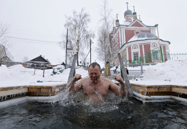 A man takes a dip in icy waters during celebrations for the Orthodox Epiphany on the Trubezh River near the church of Forty Saints, in the historic town of Pereslavl Zalessky, Russia, January 19, 2016. (Photo by Maxim Zmeyev/Reuters)
