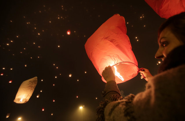 """A participant holds up a sky lantern to be released during the """"Christmas light of wishes"""" event in Zagreb, Croatia, December 17, 2016. (Photo by Antonio Bronic/Reuters)"""