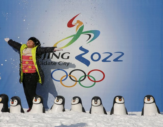 A girl throws snow into the air as she poses for her souvenir picture in front of a board celebrating Beijing as the host of the 2022 Winter Olympics, during the Ice and Snow carnival at Taoranting park in Beijing, China, January 25, 2016. (Photo by Kim Kyung-Hoon/Reuters)