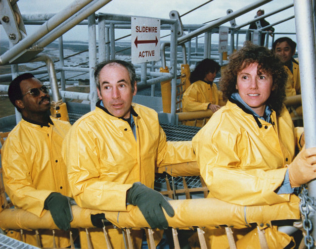 The STS-51L Challenger flight crew emergency egress training in the slide wire baskets. From left to right they are: Mission Specialist, Ronald McNair, Payload Specialist, Gregory Jarvis, Teacher in Space Participant, Christa McAuliffe. Directly behind them: Mission Specialist Judy Resnik and Mission Specialist, Ellison Onizuka. (Photo by NASA)