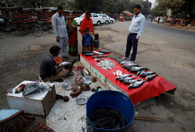 People purchase fish from a roadside vendor in New Delhi, India December 13, 2016. (Photo by Adnan Abidi/Reuters)