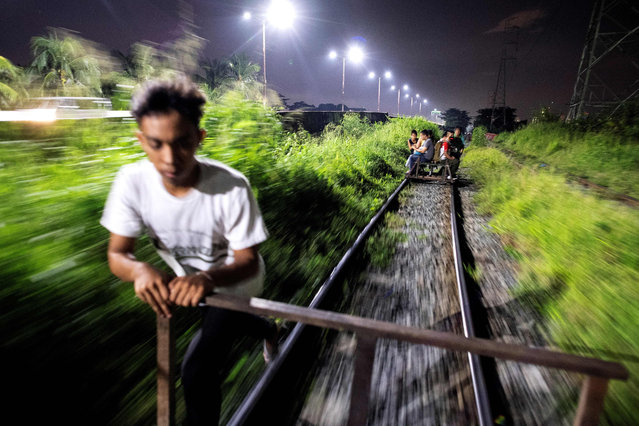 "This picture taken on October 18, 2018 shows a ""trolley boy"" pushing a home- made cart along a train track in Manila, Philippines. (Photo by Noel Celis/AFP Photo)"