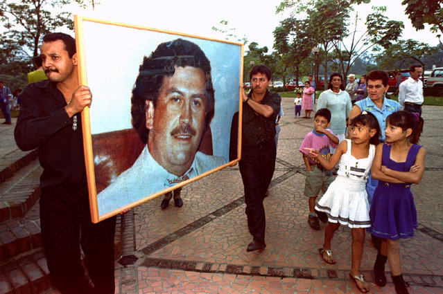 Two men carry a picture of Pablo Escobar through the streets of Medellin, Colombia on December 2, 1994 on the first anniversary of his death. Hundreds of admirers packed a memorial service for the slain cocaine king, proclaiming undying loyalty to the dead drug lord. (Photo by Jose Gomez/Reuters)