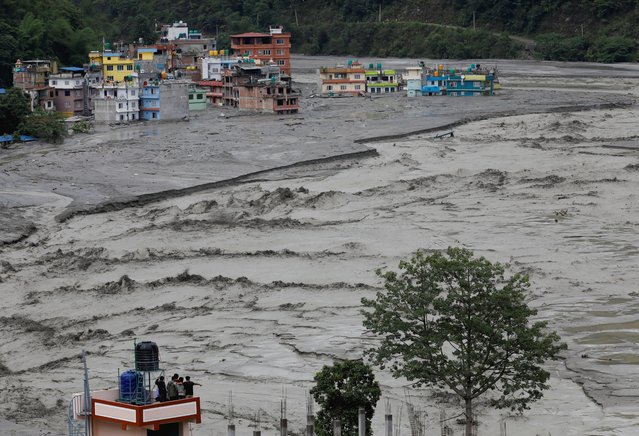 People stand on the roof of a house as flood water from the swollen Melamchi river enters the village in Sindhupalchok, Nepal on June 16, 2021. (Photo by Navesh Chitrakar/Reuters)
