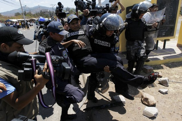 Policemen carry an injured colleague during a protest in Tegucigalpa March 25, 2015. (Photo by Jorge Cabrera/Reuters)