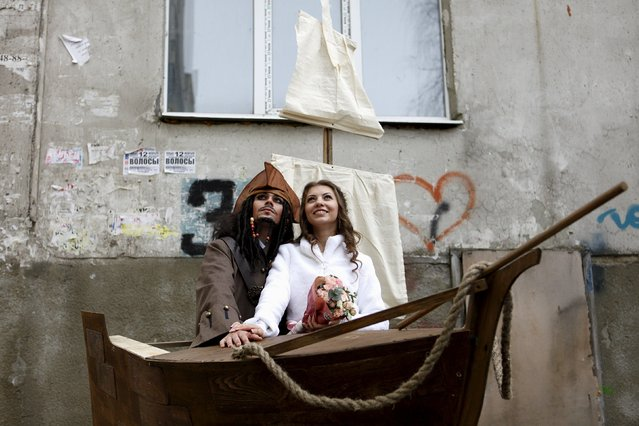 German Yesakov, 25, a cameraman from Russia, dressed as movie character Captain Jack Sparrow, and his bride Anastasiya pose with a sailing ship decoration during their wedding ceremony in the southern city of Stavropol, Russia, February 5, 2016. (Photo by Eduard Korniyenko/Reuters)