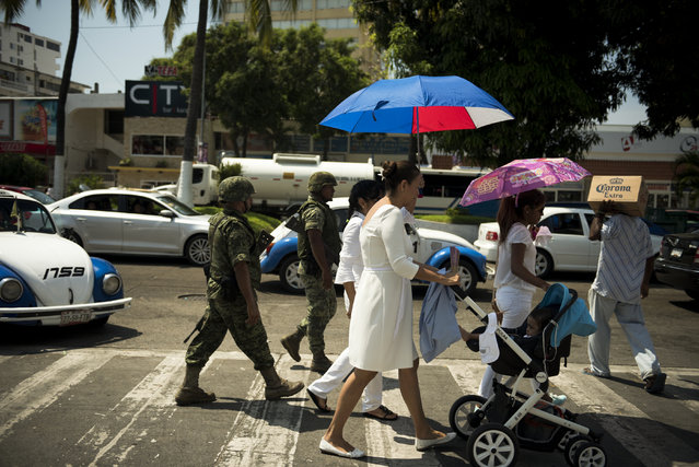 Mexican Marines follow a religious procession marking Good Friday as it makes its way down Acapulco's main boulevard on April 3, 2015 in Acapulco, Mexico. (Photo by Jonathan Levinson/The Washington Post)