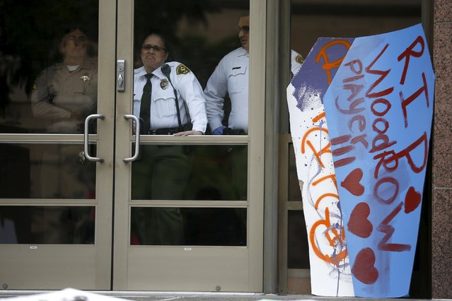 LA sheriff's deputies look out of the LA County Board of Supervisors' office where cardboard coffins were leant to commemorate the more than 617 people march organizers say have been killed by law enforcement in LA County since 2000, in Los Angeles, California April 7, 2015. (Photo by Lucy Nicholson/Reuters)