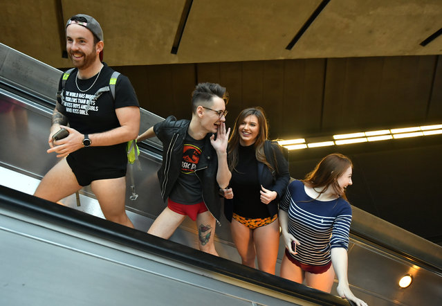 People on an escalator on the Underground as they take part in the No Trousers Tube Ride, in London on January 13, 2019. (Photo by Dominic Lipinski/PA Images via Getty Images)