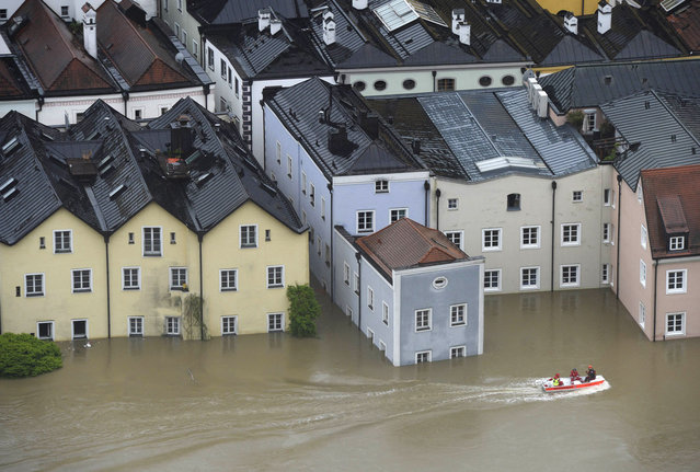 Rescue workers pass on a boat the overflooded old city of Passau, southern Germany, on June 3, 2013. Due to heavy and ongoing rainfalls, parts of the southern state of Bavaria were flooded. (Photo by Christof Stache/AFP Photo)