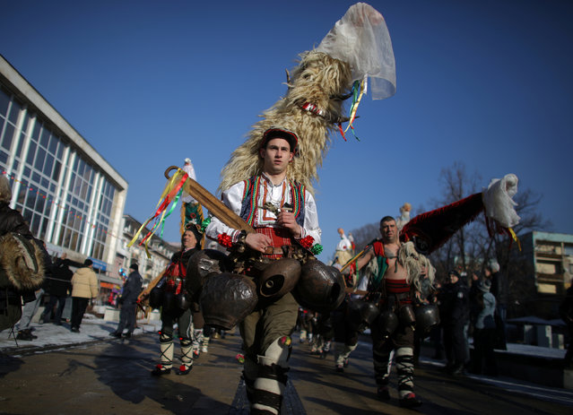 Men, carry their masks made of animal fur, as they dance during the International Festival of the Masquarade Games in Pernik, Bulgaria, January 27, 2019. (Photo by Stoyan Nenov/Reuters)