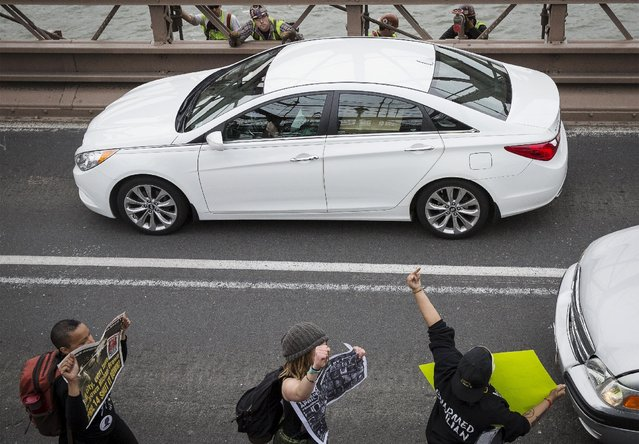 Demonstrators stop traffic on the Brooklyn Bridge during a protest against police brutality against minorities, in New York April 14, 2015. (Photo by Brendan McDermid/Reuters)
