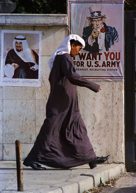 In this March 10, 1991 file photo, a poster of the Emir of Kuwait and a U.S. recruiting poster share space in a private compound, in Kuwait City. Twenty five years after the first U.S. Marines swept across the border into Kuwait in the 1991 Gulf War, American forces find themselves battling the extremist Islamic State group, born out of al-Qaida, in the splintered territories of Iraq and Syria. The Arab allies that joined the 1991 coalition are fighting their own conflicts both at home and abroad, as Iran vies for greater regional power following a nuclear deal with world powers. (Photo by John Gaps III/AP Photo)