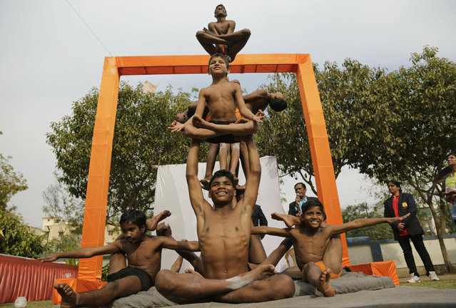 Indian boys perform Mallakhamba, a traditional Indian gymnastic sport on a vertical wooden pole, at a school in Ahmadabad, India, Thursday, January 31, 2019. The event was organized as part of an initiative by the Indian government to promote the traditional sport. (Photo by Ajit Solanki/AP Photo)